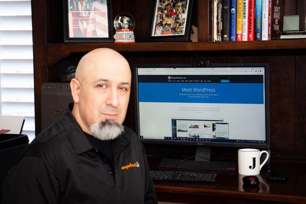 Jason Orellana in front of home desk